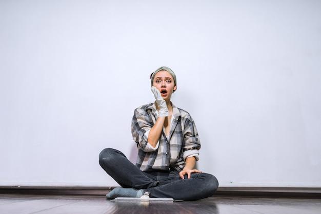 Грустная молодая девушка-строитель сидит на полу, устала делать ремонт, в резиновых перчатках