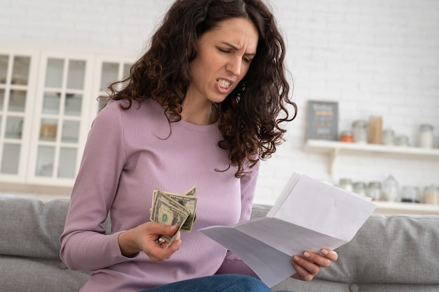 Sad young girl holding last cash money feeling anxiety about debt or bankruptcy, sitting at home.