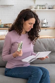 Грустная молодая девушка, держащая последние наличные деньги, чувствуя беспокойство по поводу долга или банкротства, сидя дома.