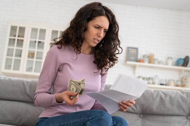 집에 앉아 부채 또는 파산에 대한 불안을 느끼는 마지막 현금 돈을 들고 슬픈 어린 소녀