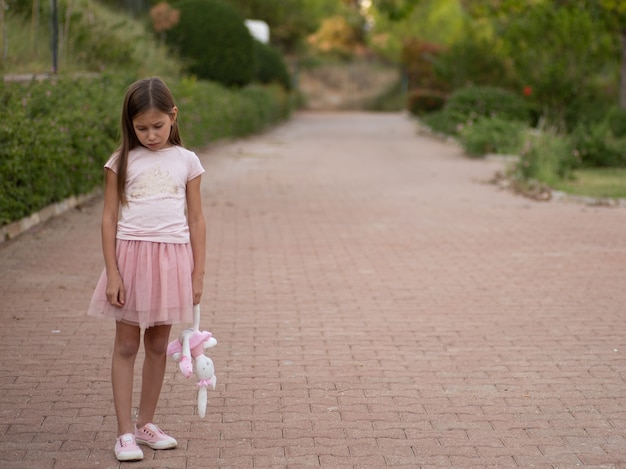 Sad young girl holding toy