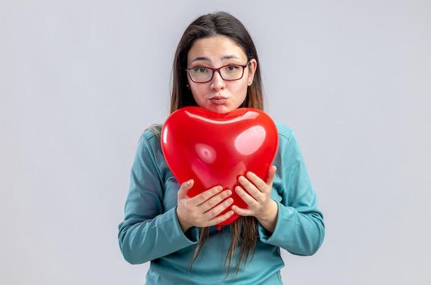 흰색 배경에 고립 된 심장 풍선을 들고 발렌타인 데이에 슬픈 어린 소녀