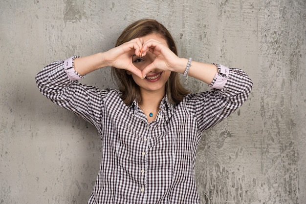 Sad young girl in plaid shirt showing heart with hands