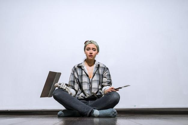 Грустная молодая девушка сидит на полу, держа в руках шпатели, устала делать ремонт