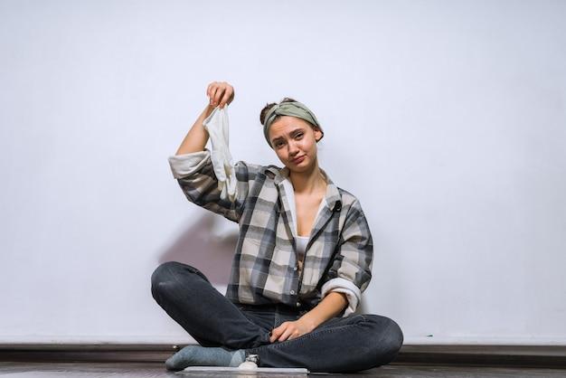 Грустная молодая девушка сидит на полу, устала делать ремонт, сняла перчатки