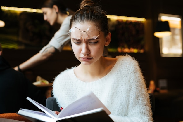 Sad young girl student in glasses and in white sweater teaches lectures in cafe