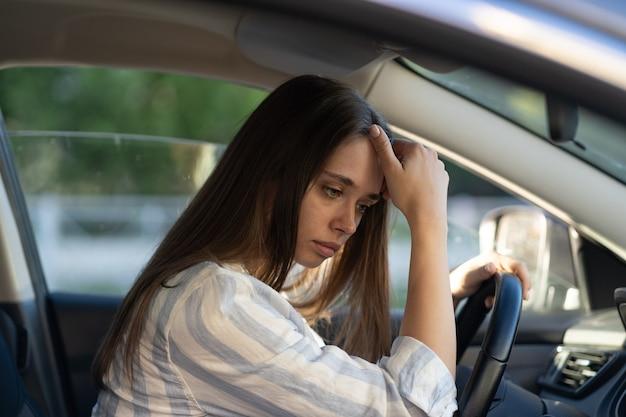 슬픈 어린 소녀는 스트레스를 받은 운전 자동차 불행한 여성 운전자가 직장이나 공부에서 문제를 생각합니다