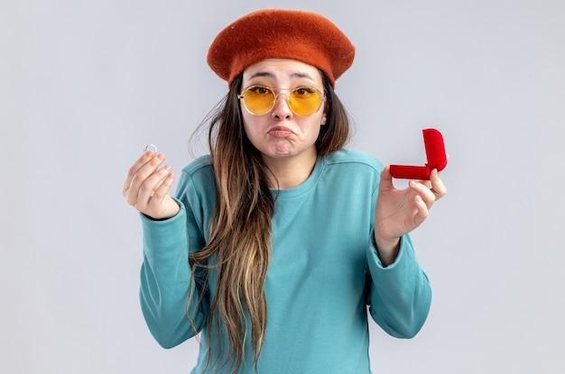Ragazza triste il giorno di san valentino che indossa un cappello con gli occhiali che tengono l'anello nuziale isolato su sfondo bianco