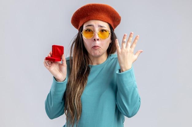 La ragazza triste il giorno di san valentino che indossa un cappello con gli occhiali indossa la fede nuziale isolata su sfondo bianco white
