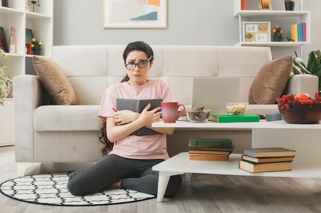 リビングルームのコーヒーテーブルの後ろの床に座っているノートブックを保持している眼鏡をかけている悲しい少女