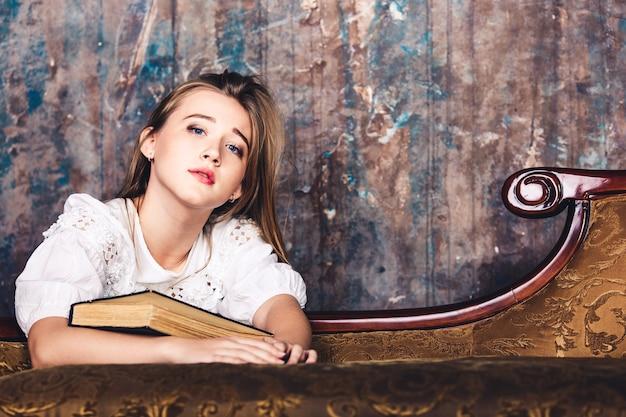 그녀의 손에있는 책을 가진 슬픈 어린 소녀. 공부에 지친 학생.