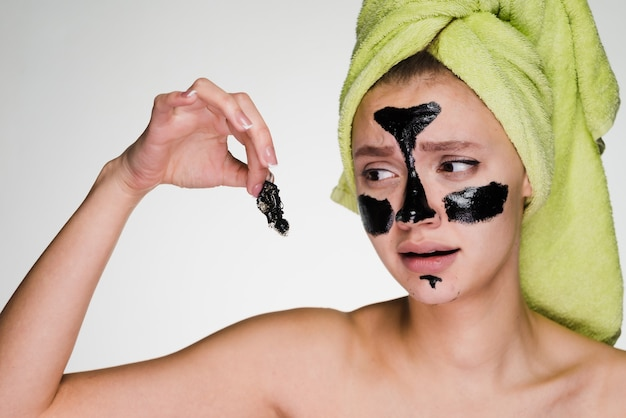 Sad young girl with a green towel on her head removes a black mask from her face, it hurts