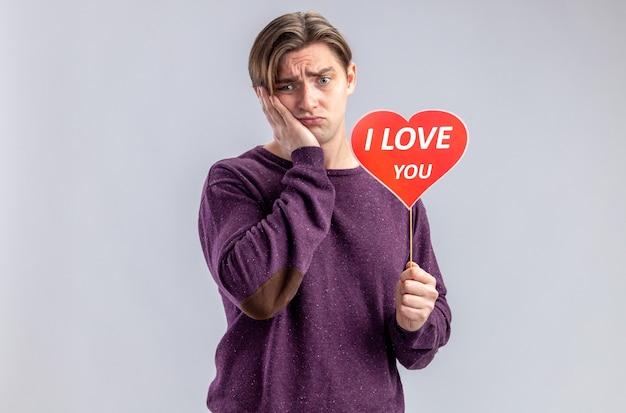 Triste giovane ragazzo il giorno di san valentino che tiene il cuore rosso su un bastone con ti amo testo mettendo la mano sulla guancia isolato su sfondo bianco