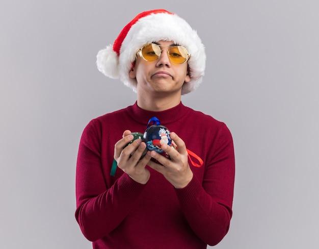 Ragazzo giovane triste che porta il cappello di natale con gli occhiali che tengono le palle dell'albero di natale isolate su fondo bianco