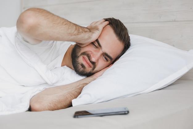 Грустный молодой красивый бородатый мужчина, лежащий в постели с белым листовым одеялом в спальне дома