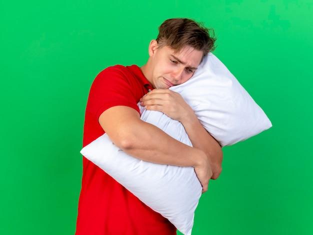Triste giovane bella bionda uomo malato abbracciando cuscino guardando verso il basso isolato su sfondo verde