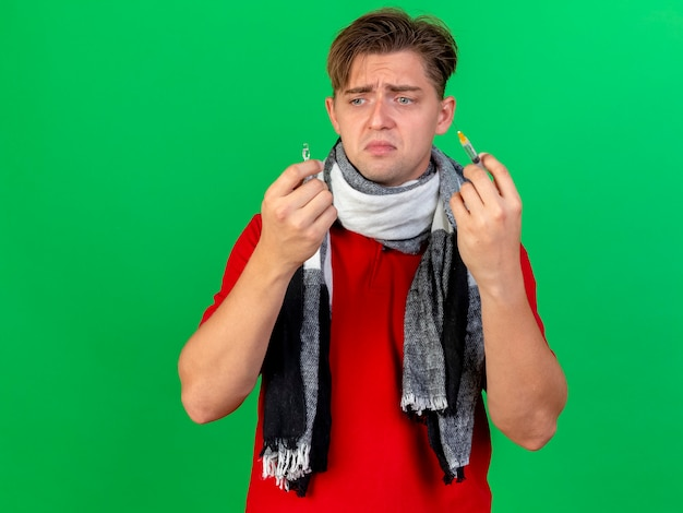 Sciarpa da portare della sciarpa della tenuta dell'uomo malato bello giovane triste e fiala medica che esamina la fiala isolata sulla parete verde con lo spazio della copia