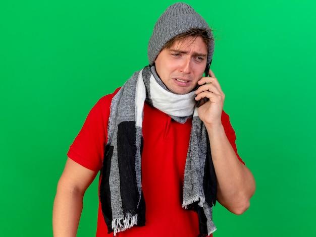 겨울 모자와 스카프를 쓰고 슬픈 젊은 잘 생긴 금발 아픈 남자가 녹색 배경에 고립 된 측면을보고 전화로 이야기