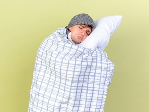 冬の帽子とスカーフを身に着けている悲しい若いハンサムな金髪の病気の男は、オリーブグリーンの背景に分離された目を閉じて頭を置く枕を保持している格子縞に包まれています