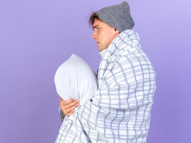 冬の帽子とスカーフを身に着けている悲しい若いハンサムな金髪の病気の男は、コピースペースで紫色の背景にまっすぐに分離された枕を保持している縦断ビューで立っている格子縞に包まれています