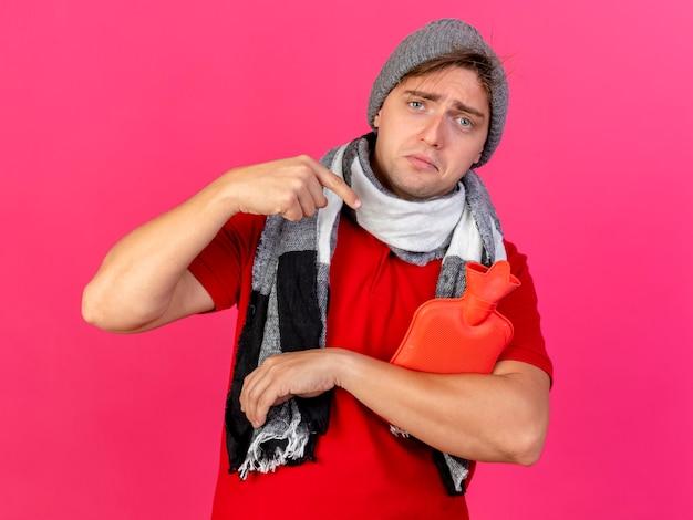 Uomo malato biondo bello giovane triste che indossa cappello e sciarpa di inverno che guarda l'obbiettivo della macchina fotografica e che indica alla bottiglia di acqua calda isolata su fondo cremisi
