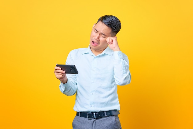 Sad young handsome businessman playing a game on mobile phone on yellow background