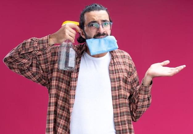Triste giovane bel ragazzo delle pulizie che indossa t-shirt tenendo uno straccio in bocca e mettendo il flacone spray sul tempio diffondendo la mano isolata sul muro rosa