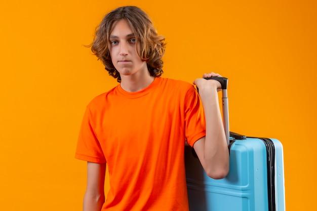 노란색 배경 위에 서 불행한 얼굴로 카메라를보고 여행 가방을 들고 오렌지 티셔츠에 슬픈 젊은 잘 생긴 남자