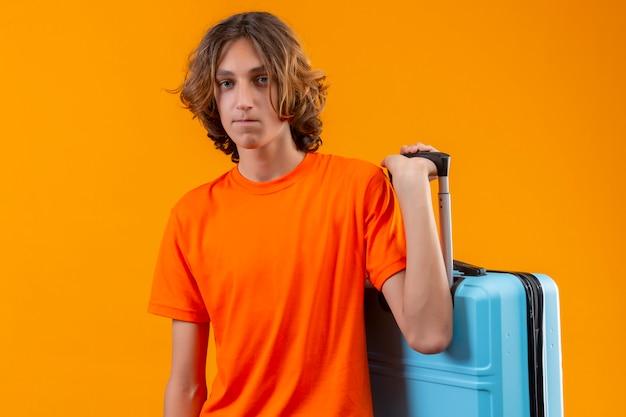 不幸な顔立ちでカメラを見て旅行スーツケースを保持しているオレンジ色のtシャツで悲しい若いハンサムな男