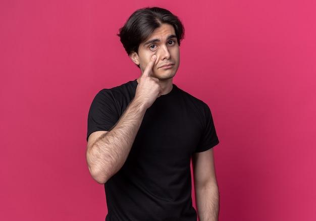 Triste giovane bel ragazzo che indossa una maglietta nera che tira giù la palpebra isolata sul muro rosa