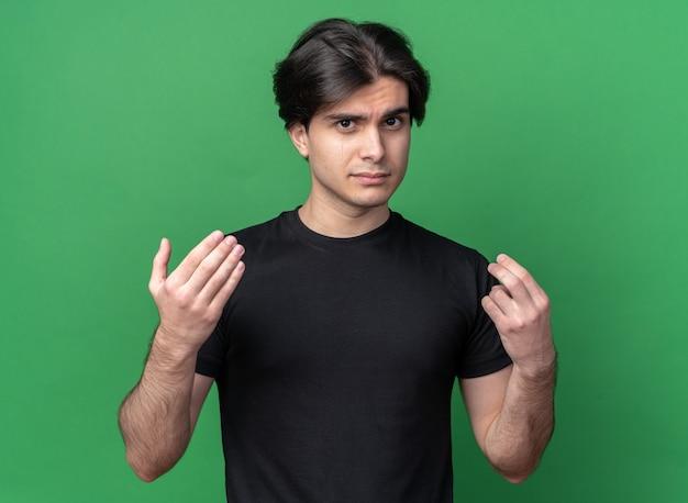 녹색 벽에 고립 된 팁 제스처를 보여주는 검은 티셔츠를 입고 슬픈 젊은 잘 생긴 남자
