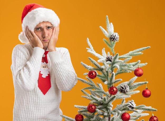 오렌지 배경에 고립 된 카메라를보고 얼굴에 손을 유지 장식 된 크리스마스 트리 근처에 서 크리스마스 모자와 산타 클로스 넥타이를 입고 슬픈 젊은 잘 생긴 남자