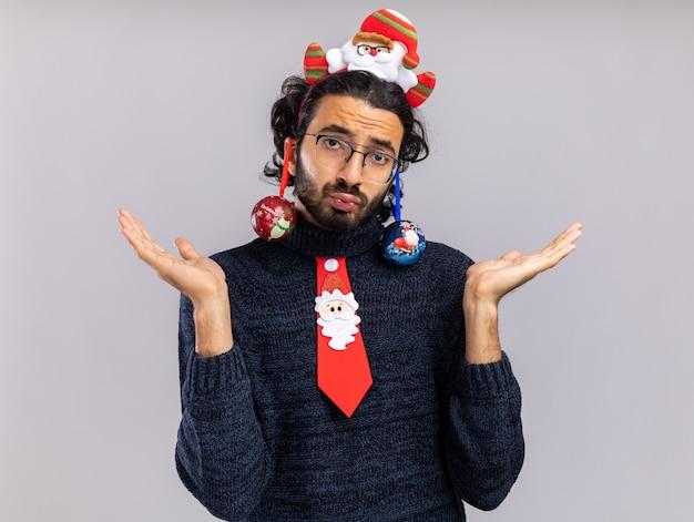 Triste giovane bel ragazzo indossa cravatta natalizia con cerchio per capelli appeso palla di natale sulle orecchie diffondendo le mani isolate su sfondo bianco