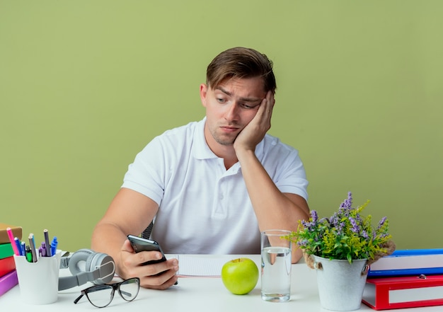 Sad young handsome male student sitting at desk with school tools holding and looking at phone isolated on olive green