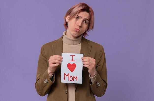 Грустный молодой красивый мужчина держит письмо для своей мамы