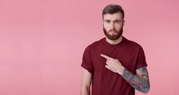 Triste giovane bell'uomo barbuto rosso in camicia rossa, vuole attirare la tua attenzione, puntando le dita a sinistra nello spazio della copia, si trova su sfondo rosa con le labbra verso il basso.