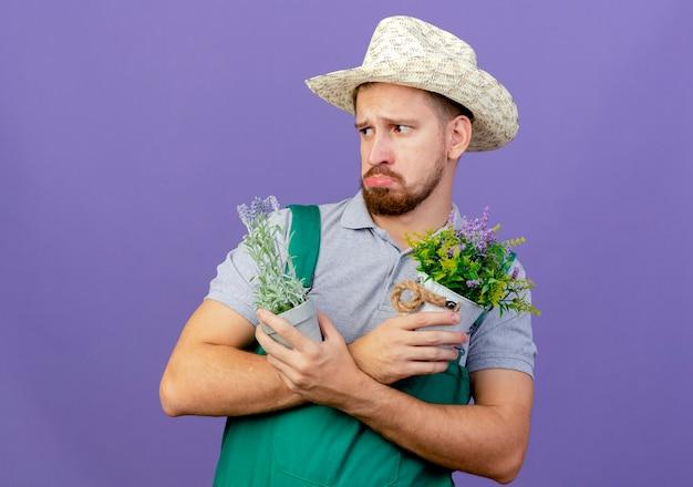 制服を着た悲しい若いハンサムなスラブの庭師とコピースペースで紫色の壁に隔離された側を見て植木鉢を持って手を交差させた帽子