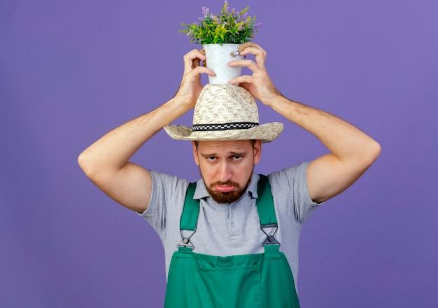 Giardiniere slavo bello giovane triste in uniforme e cappello che tiene vaso di fiori sulla testa isolata sulla parete viola