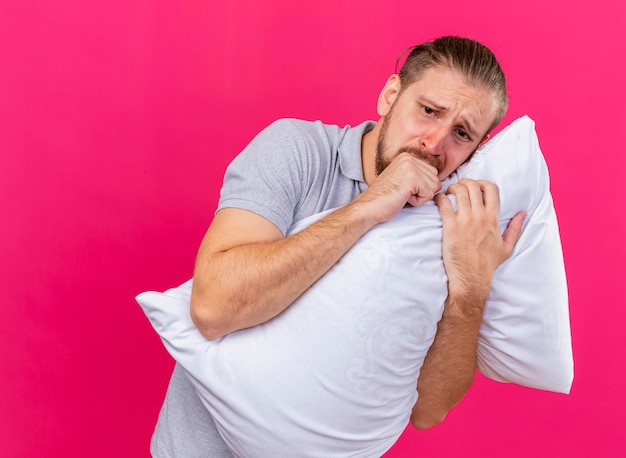 Sad young handsome slavic ill man hugging pillow looking straight coughing keeping fist near mouth isolated on pink wall with copy space