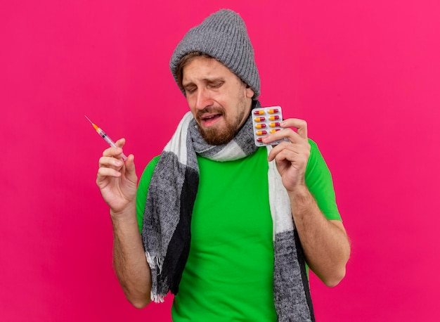 Sad young handsome slavic ill man wearing winter hat and scarf holding syringe and pack of capsules with closed eyes isolated on pink wall with copy space