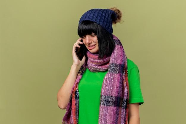 Triste giovane ragazza caucasica malata indossando cappello invernale e sciarpa parlando al telefono guardando verso il basso isolato su sfondo verde oliva con spazio di copia