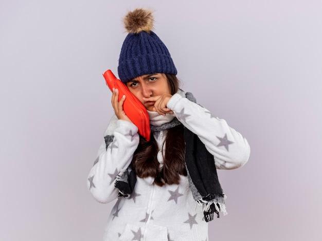 Triste giovane ragazza malata guardando lato indossando il cappello invernale con sciarpa che mette la borsa dell'acqua calda sulla guancia