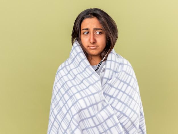 Triste giovane ragazza malata guardando lato avvolto in un plaid isolato su verde oliva