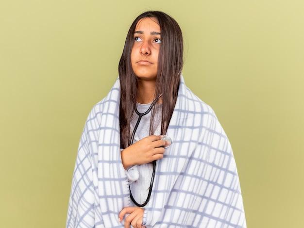 Грустная молодая больная девушка смотрит вверх, завернутая в плед, одетая и слушая свое собственное сердцебиение со стетоскопом, изолированным на оливково-зеленом фоне