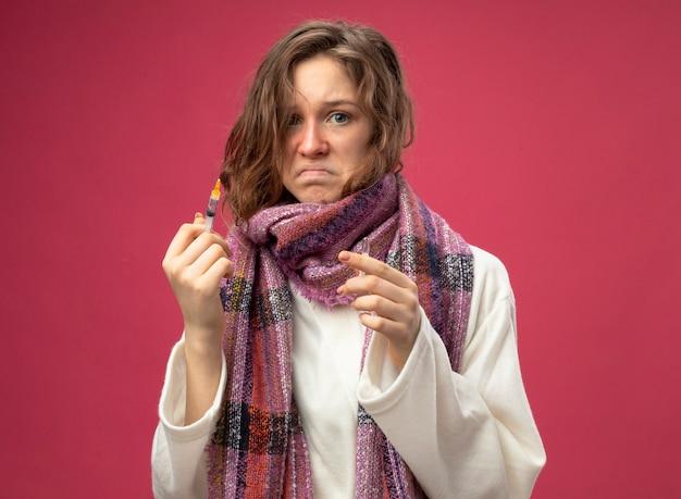 Грустная молодая больная девушка в белом халате и шарфе держит шприц с ампулой, изолированной на розовой стене