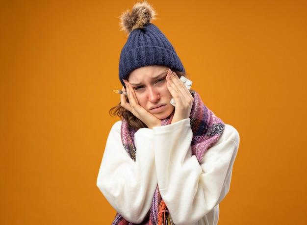 オレンジ色に分離されたアジアのジェスチャーを示す錠剤と注射器を保持しているスカーフと白いローブと冬の帽子を身に着けている悲しい若い病気の女の子