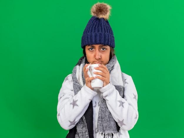 緑の背景で隔離のお茶のカップを保持しているスカーフと冬の帽子をかぶって悲しい若い病気の女の子