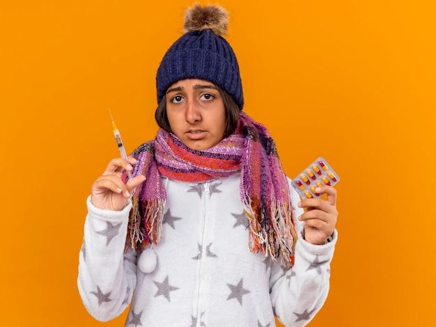 Triste giovane ragazza malata che indossa il cappello invernale con sciarpa tenendo la siringa con le pillole isolato su sfondo giallo