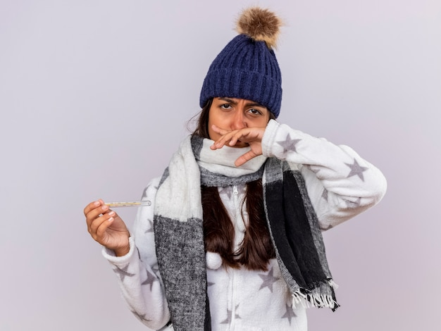Sad young ill girl wearing winter hat with scarf holding thermometer and wiping nose with hand isolated on white background