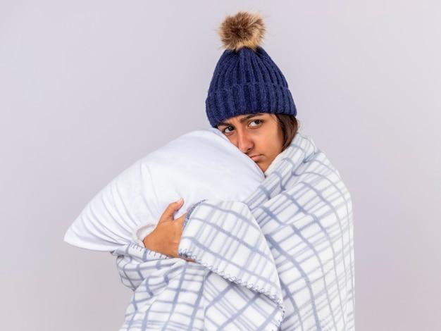 스카프와 겨울 모자를 쓰고 슬픈 어린 아픈 소녀는 흰색에 고립 된 격자 무늬 포옹 베개에 싸여